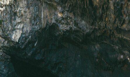Man looking at a large rock wall